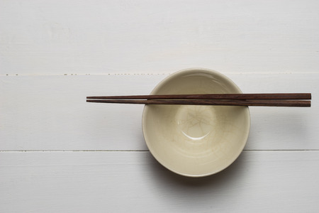 chop sticks: empty bowl with chop sticks on wooden white table Stock Photo