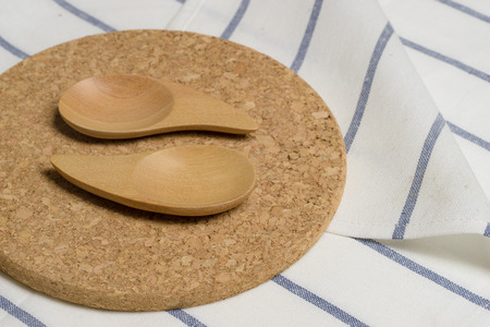 Wooden kitchen spoon on a cork plate and white napkin photo