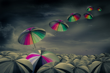 rainbow umbrella in the mass of black umbrellas Stock Photo