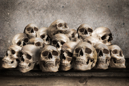 Stacked human skulls on old wooden table in front of grunge concrete wall photo