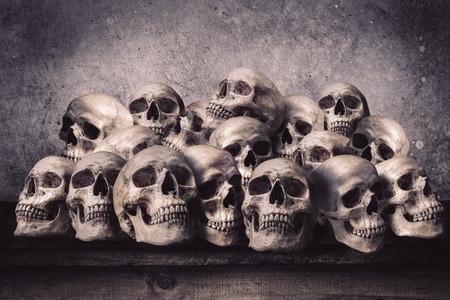 Gestapelte menschliche Schädel auf alten Holztisch vor der Grunge Betonwand Standard-Bild - 39336348