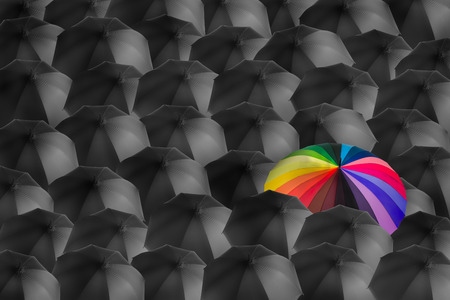 rainbow umbrella in mass of black umbrellas, different concept Stock Photo