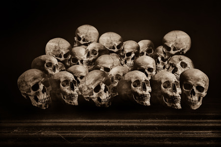genocide: Human skulls on grunge wooden table Stock Photo
