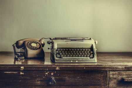 Vintage typewriter, telephone,on table desaturated photo photo