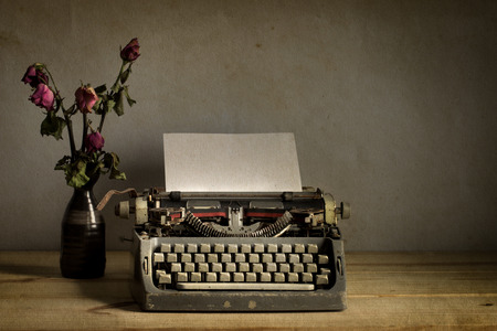 maquina de escribir: Naturaleza muerta con m�quina de escribir vieja con seco flores color de rosa en la mesa de madera