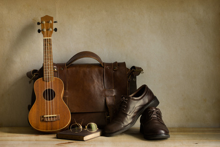 Still life with leather suitcase, brown shoes, ukulele and old glasses on the book, vintage style Stock Photo