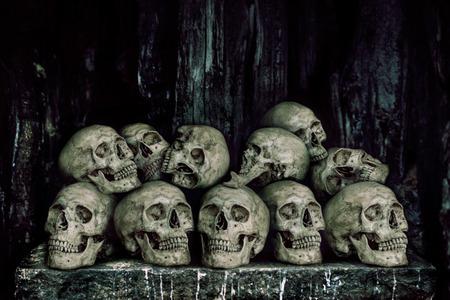 sacrificio: Pila de cr�neos humanos en la mesa de piedra para el sacrificio con la cera de oro y una vela