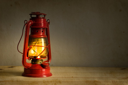 hurricane lamp: Old fashioned lantern on wooden table