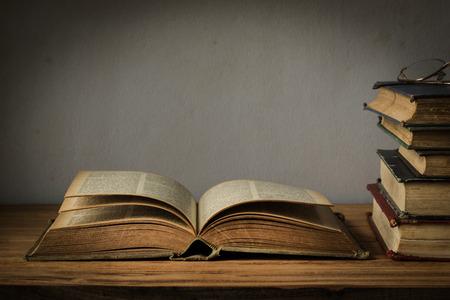 libros antiguos: viejo libro abierto sobre una mesa de madera con vidrios