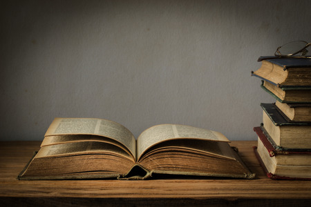 old book open on a wooden table with glasses
