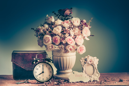 love life: Still life with retro clock and flowers, flake, and love letter on wooden table