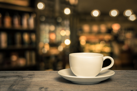 cup of coffee on wooden table with defocus bokeh of coffee shop background Stock Photo