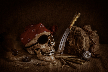 ancient ships: Still life, pirate skull with cigar in the mouth, compass on ancient map, knife and pocket watch hang on the log