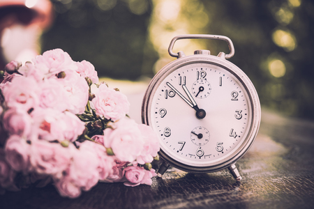 Old alarm clock on wooden table with pink rose, defocus shooting