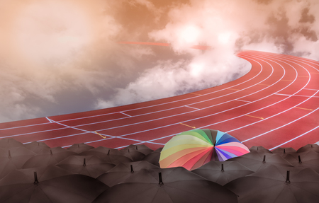 Rainbow umbrella in race field toward into sky with clouds, competition or leadership concept Stock Photo