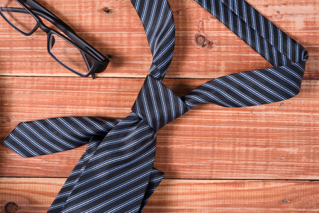 neck tie: Stripe neck tie and glasses on old wooden table