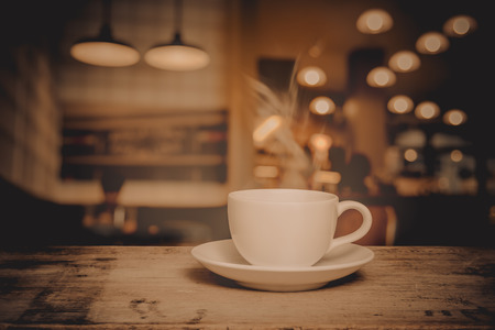 cup of coffee on table in cafe, vintage style