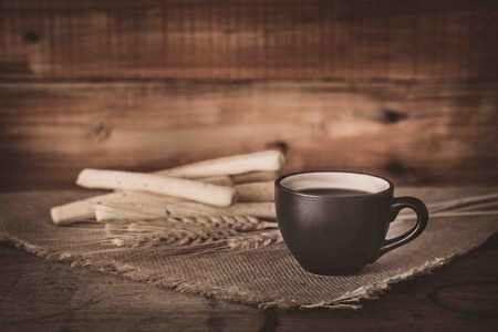 breadsticks: Coffee cup and breadsticks on old wooden background