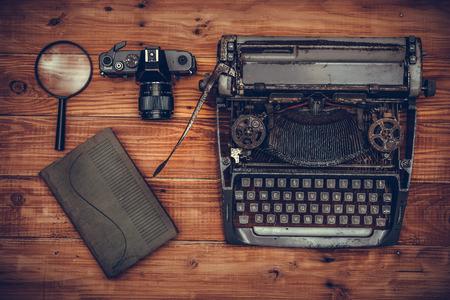 maquina de escribir: Vista superior de la máquina de escribir vieja, cámara vieja, lupa y libro sobre fondo de madera