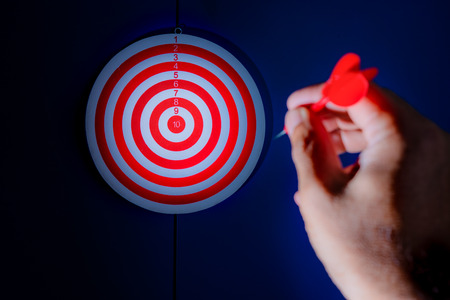 achieve: Red dart in man hand point to target on the blue wall, selective focus on dart target, concept to win