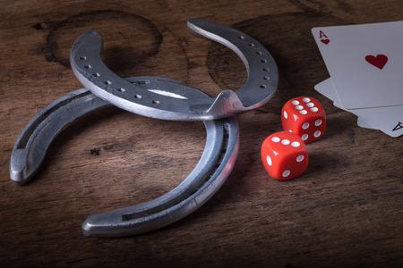 herradura: Dados Lucky Dados juego el despliegue de números nueve y póker de la vendimia de azar tarjetas con ganar ases de herraduras viejas para el jugador y jugador buena suerte encanto en la mesa de madera rústica en el salón de juego occidental