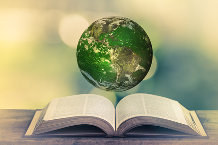 vacance: Planet over the open book on a wooden table in nature, green blurry background. World Environment Day. World Mental Health Day concept. Elements of this image furnished by NASA. Stock Photo