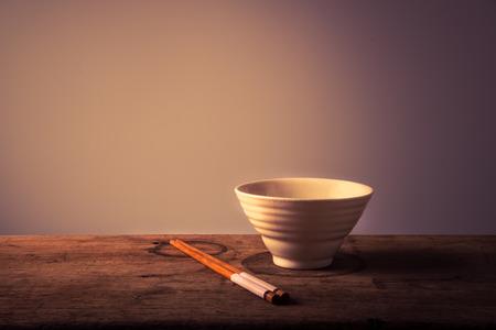 나무 테이블에 젓가락으로 빈 흰색 그릇