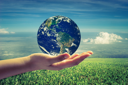 Planet in human hands on beautiful green meadow and blue sky background. World Environment Day. World Mental Health Day concept. Elements of this image furnished by NASA.