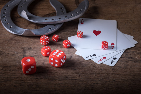 good luck charm: Lucky craps game dice rolling out chance number nine and vintage poker cards with winning aces by old horseshoes for player and gambler good luck charm on rustic wood table in western gambling saloon Stock Photo