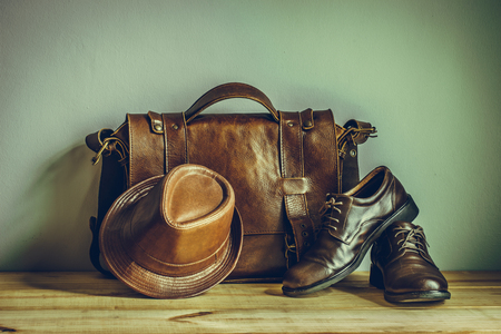Still life with leather suitcase, brown shoes, and old glasses on the book, vintage style