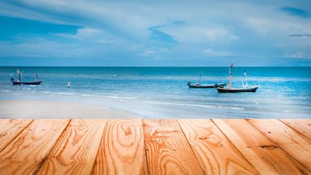 fishery products: Wood table top on beach with fishery boats in sea - can be used for display or montage your products