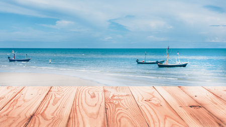 Wood table top on beach with fishery boats in sea - can be used for display or montage your products