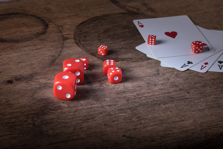 gambler: Lucky craps game dices and vintage poker cards with winning aces and gambler good luck charm on rustic wood table in western gambling saloon Stock Photo