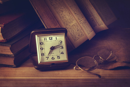 come in: An antique pocket watch, glasses and books come together in this vintage still life.