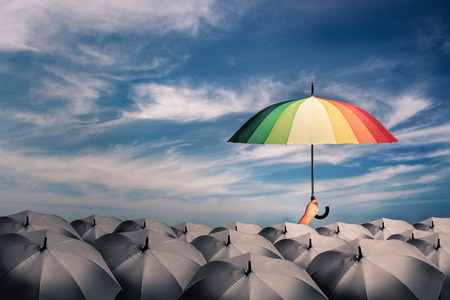 rainbow umbrella in mass of black umbrellas, concept for creative ideas or leadership and different