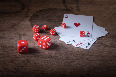 Lucky craps game dices and vintage poker cards with winning aces and gambler good luck charm on rustic wood table in western gambling saloon Stock Photo