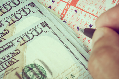 lottery win: Man hand marking down to select number in lotto ticker with dollar bill