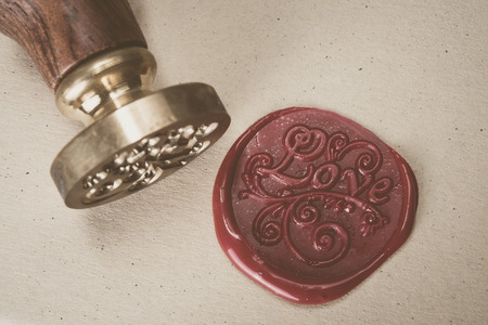 Love letter and ornament on red wax seal over brown paper with copyspace Archivio Fotografico