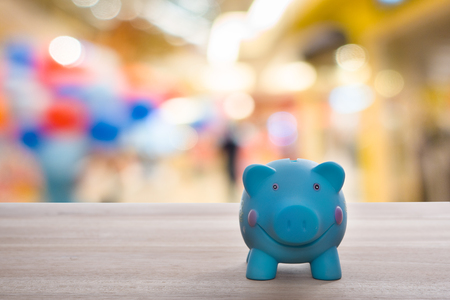 economic crisis: piggy bank with shopping mall background, abstract background to time to start to saving or solution for keep money for economic crisis. Stock Photo