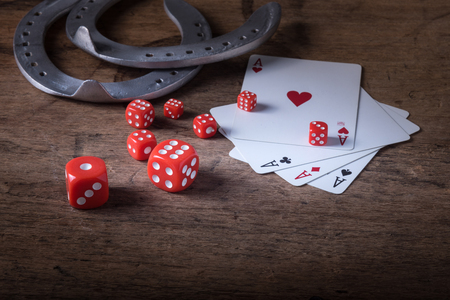 gambler: Lucky craps game dice rolling out chance number nine and vintage poker cards with winning aces by old horseshoes for player and gambler good luck charm on rustic wood table in western gambling saloon Stock Photo