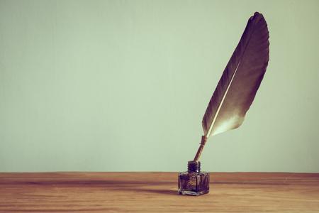 Vintage alten Federkiel, Tintenfass auf Holztisch. Vintage-Stil gefiltert Foto Standard-Bild