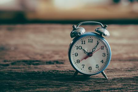 Vintage alarm clock on weathered wood background