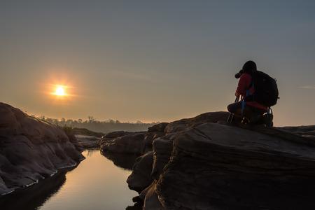 female photographer: Female photographer taking photo on the rock with sunrise landscape Stock Photo