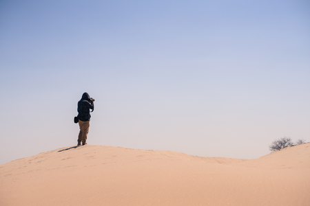 nature photo: Man taking photo in desert with clear blue sky Stock Photo