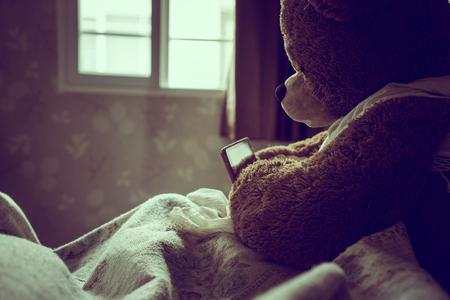oso caricatura: Peluche oso uso de la tableta en la cama, por efecto de estilo de la vendimia Foto de archivo