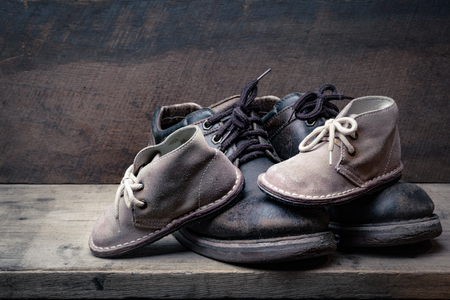 Brown shoes of daddy and son on on wooden table, bar or counter over brown wood wall background, fathers day conceptual Stock Photo