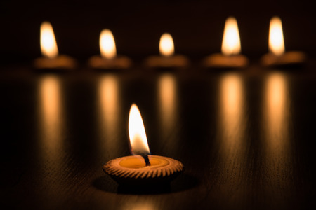 Candle light in clay pot on wooden background in the dark, selective focus
