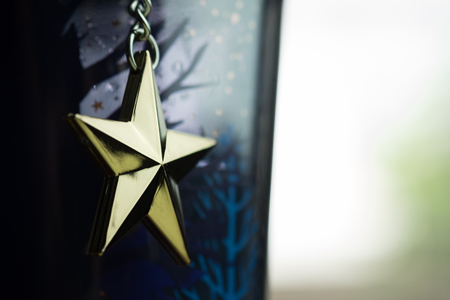 Golden star hang on chain with bright vintage background