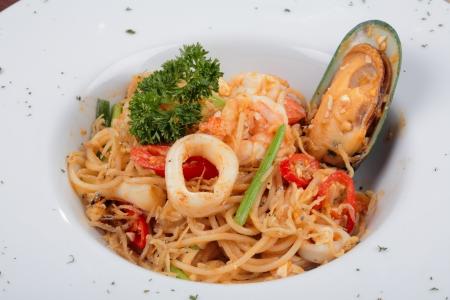 Macaroni or spaghetti with ingredients on white plate photo