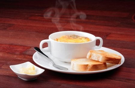 Onion soup and bread in breakfast set which on top of the table.